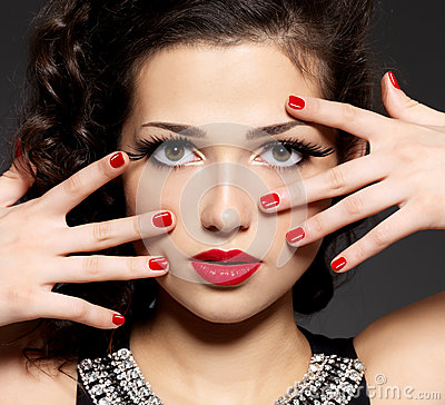 Brunette woman with red nails and makeup