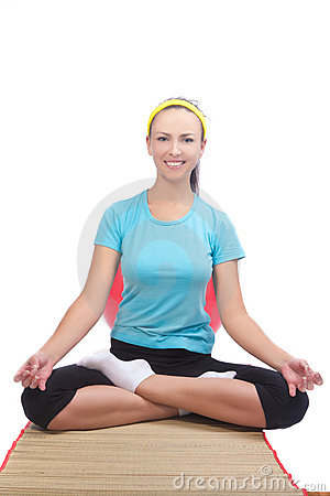Brunette woman sitting on mat and doing yoga
