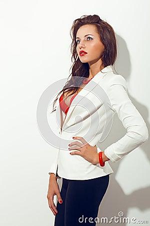 Brunette woman standing near white wall