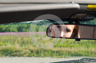 Brunette woman watching on rear-view mirror