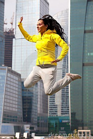 Brunette in a yellow blazer jumping