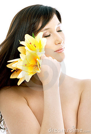 Brunette with yellow lily flowers in spa