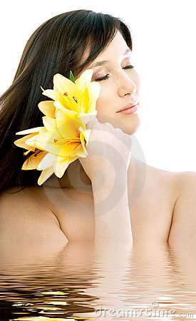 Brunette with yellow lily flowers in water