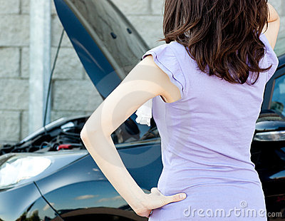 Brunette young woman standing in front of her car