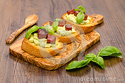 Bruschette with avocado cream and sausage