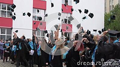 BUCAREST, ROUMANIE, MAI 2016 Image brouillée des étudiants jetant des chapeaux dans le ciel, lycée de graduation Benjamin Frankli banque de vidéos