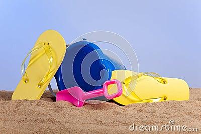 Bucket, shovel and flipflops on the beach