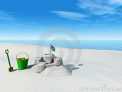 Bucket, spade and sand castle on a beach.