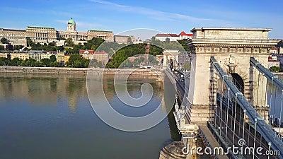 Budapest, Hungría: 4K sobrevolando el Puente de la Cadena Szechenyi con tráfico matutino ocupado al amanecer Bastión de pescadore almacen de metraje de vídeo