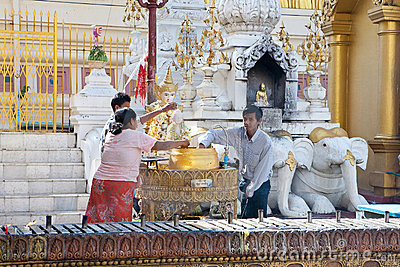 Buddhist family devotees pours water to statue of Editorial Image