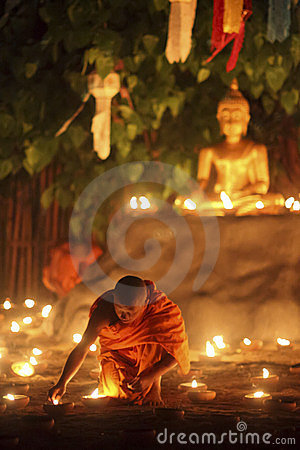 Buddhist monk fire candles to Buddha Editorial Photography