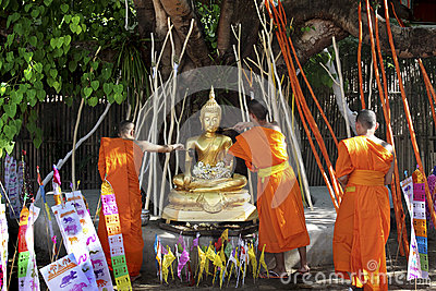 Buddhist monk pouring to Buddha statue Editorial Stock Photo