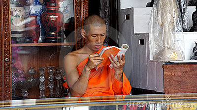 Buddhist monk is reading a book inside a shop Editorial Stock Photo