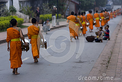 Buddhist novices walk to collect alms and offerings, Luang Prabang, Laos. Editorial Photography
