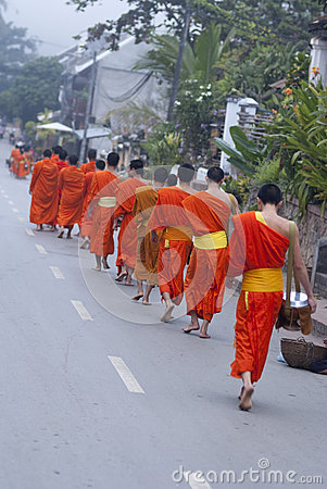 Buddhist novices walk to collect alms and offerings, Luang Prabang, Laos. Editorial Photo