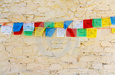 Buddhist tibetan prayer flags against wall