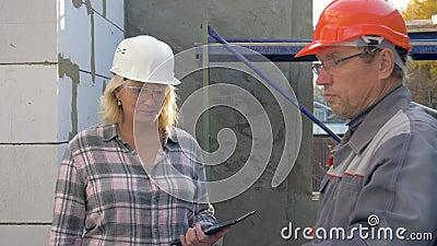 Budowniczy i klient sprawdzamy budynek w budowie wśrodku pokojów w zbiory wideo