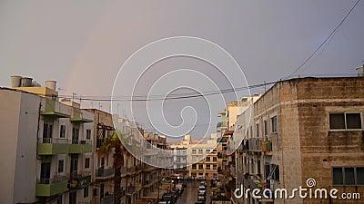 Buggiba, Malta 30 possono gli edifici residenziali 2019 del ower dell'arcobaleno il giorno tempestoso piovoso nuvoloso scuro stock footage