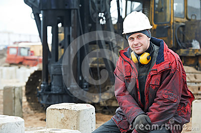 Builder in dirty workwear at construction site