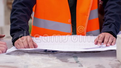 Building plan lying on the bricks. blueprints. Building plan lying on the bricks. Engineers and construction workers studying drawing. Close-up stock video footage