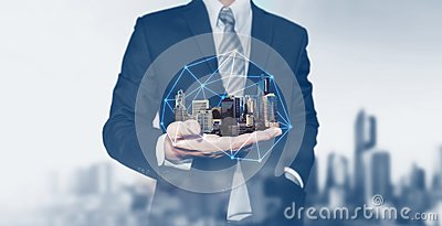 Building technology and business real estate investment. Businessman holding buildings on hand Stock Photo