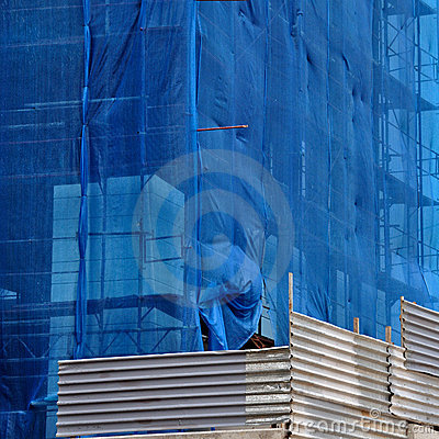 Building under debris netting at construction site