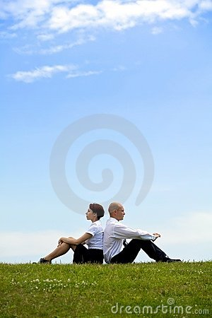 Buisness couple sitting back to back on grass