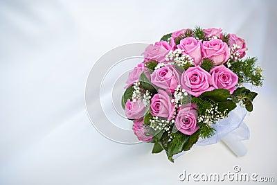 Bukett av rosa ro på den vita bröllopsklänningen