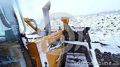 Buldożeru maszynowy działanie z ziemią na śnieżnym zima dniu Widok od kabiny zbiory wideo