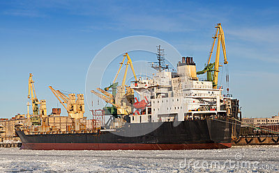 Bulk cargo ship loading in winter port