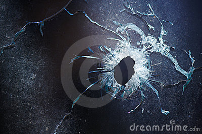A bullet hole is in glass