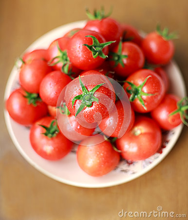 Bunch of fresh tomatoes with drops on a plate