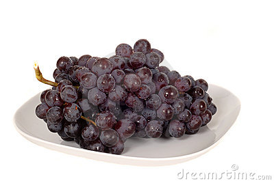 A bunch of juicy red grapes on a white plate