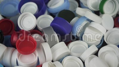 Bunch of multi coloured bottle caps. Vertical panoramic shot. Waste and recycling concept. White, blue, grey, green, black stock video