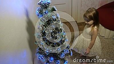 Buon concetto di infanzia Piccoli giochi di un albero di Natale nella stanza dei bambini bellissimo albero di Natale artificiale archivi video