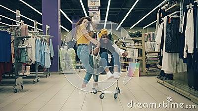 Buon divertimento nello shopping Due belle signore ballano con un carrello in un negozio di abbigliamento video d archivio