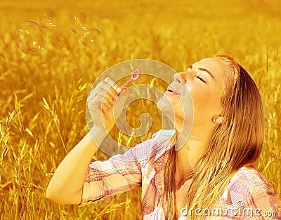 Burbujas de jabón de la muchacha que soplan en campo de trigo