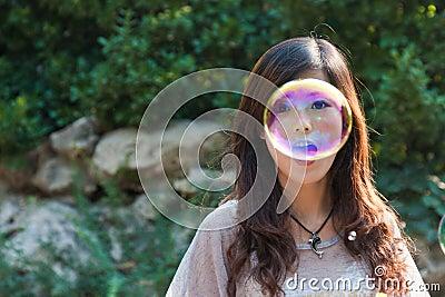 Burbujas que soplan de la muchacha hermosa joven en la naturaleza