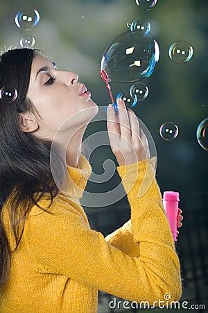Burbujas que soplan de la mujer joven