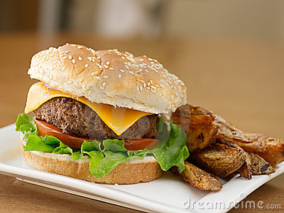 Photo of a burger with potato wedges (selective focus on beef patty).
