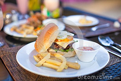 Burger and fries on white plate for lunch