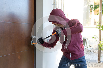 Burglar trying to force a door lock Stock Photo