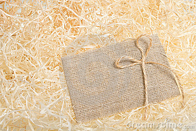 Burlap tag on straw background.