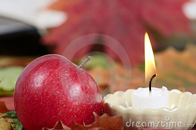 Burning candle with a red apple
