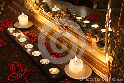 Burning candles and beads lie near mirror