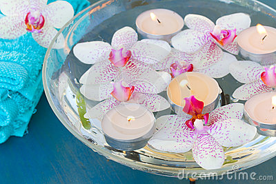 Burning  candles and pink  orchid flowers close up