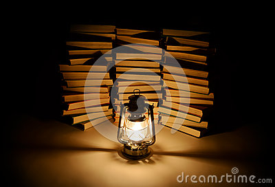 Burning kerosene lamp and books