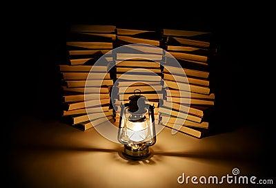 Burning kerosene lamp and books