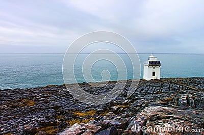 Burren lighthouse on the rocky coast of ireland.