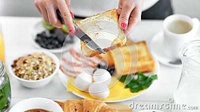 Burro di diffusione della mano femminile del primo piano sul pane tostato del pane fritto facendo uso del coltello che gode dell' video d archivio